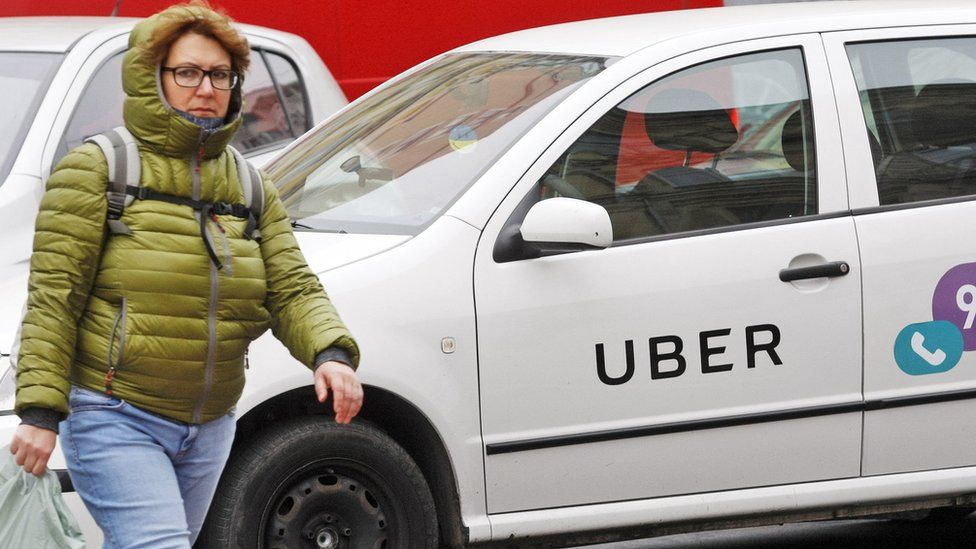 A woman seen walking next to a white car with a logo of Uber taxi cab company in Kiev, Ukraine.