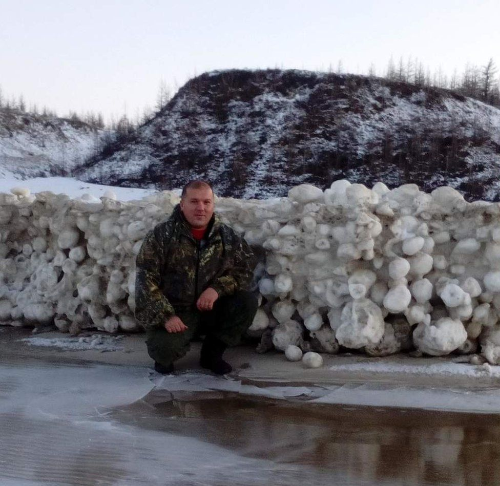 """A picture of Alexei Primak crouching by a """"snowball wall"""" formed from the icy spheres."""