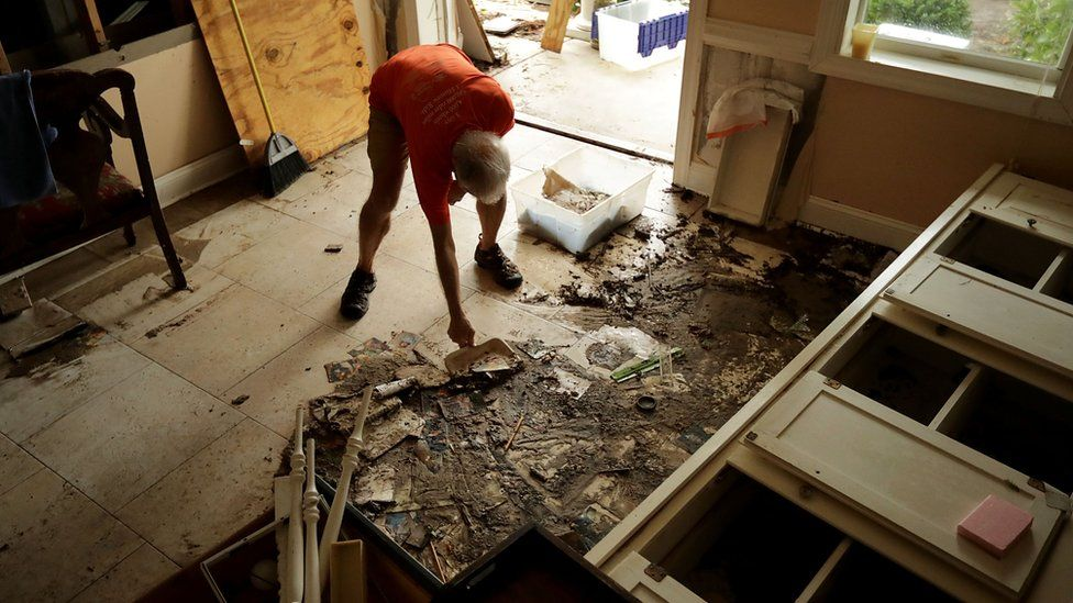 An elderly man bends down to clear debris and mud from his home