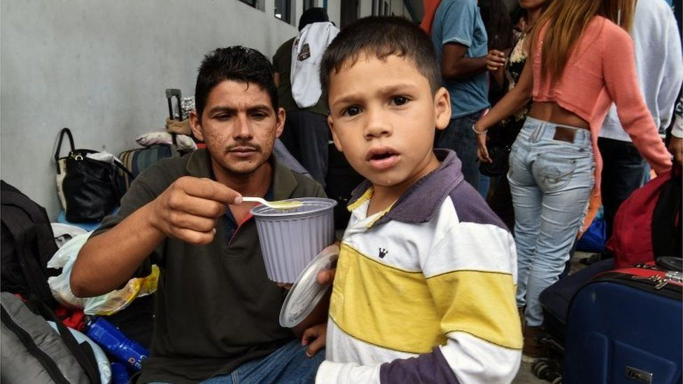 A Venezuelan migrant feeds his child, as they wait at the binational border attention centre (CEBAF) in Tumbes, northern Peru