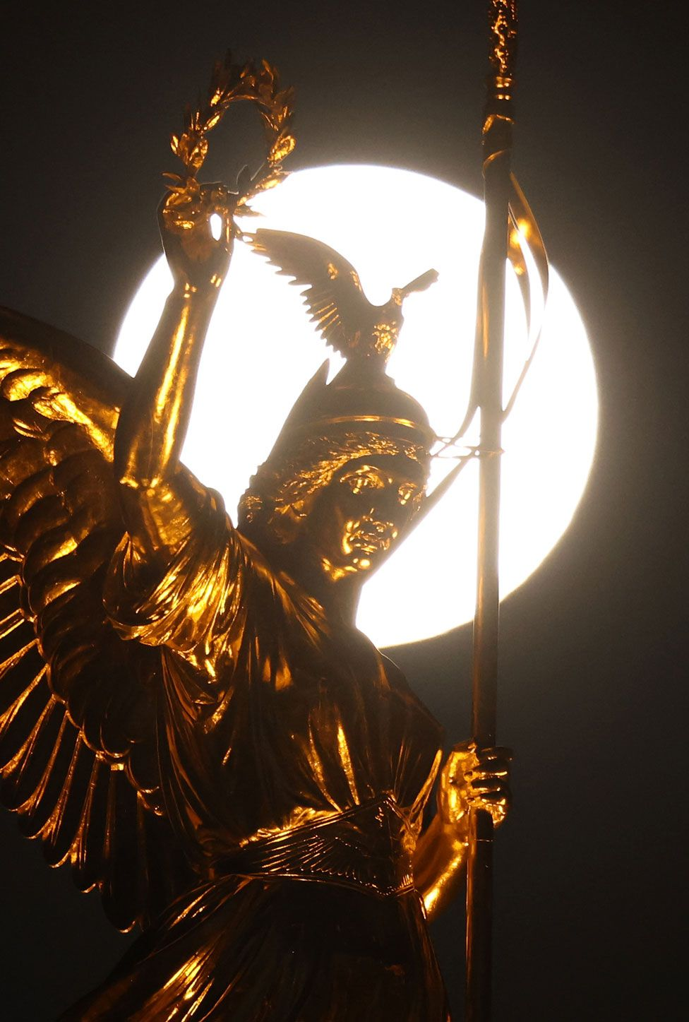 The statue of Victoria on top of the Victory Column in Berlin, Germany, is seen with the pink supermoon behind it