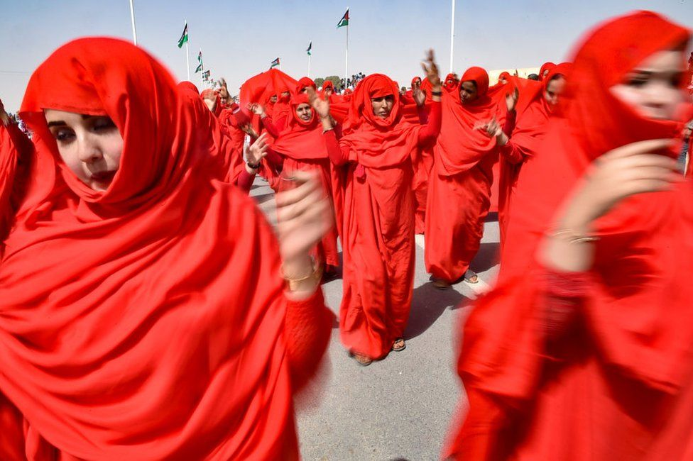 Sahrawi women perform a dance in the parade. They are fully clothed in red.