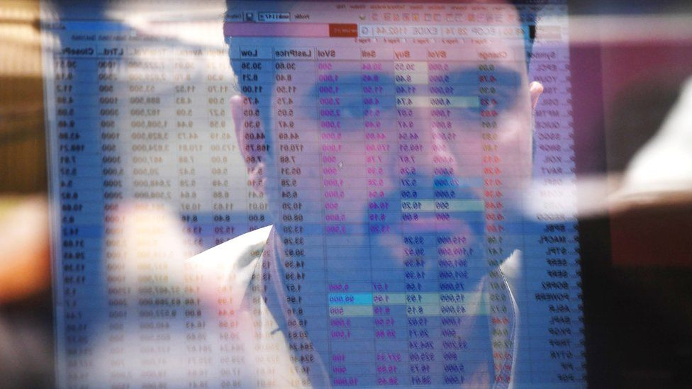 A Pakistani stockbroker is reflected in a monitor as he watches share prices during a trading session at the Pakistan Stock Exchange (PSX) in Karachi on May 24, 2017