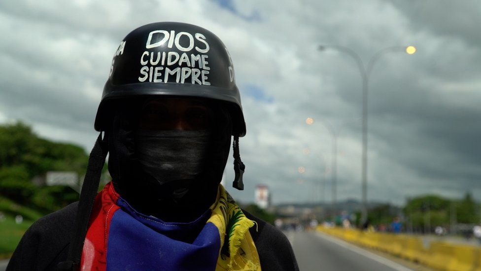 """A protester with a helmet reading """"God, protect me always"""" in Caracas"""