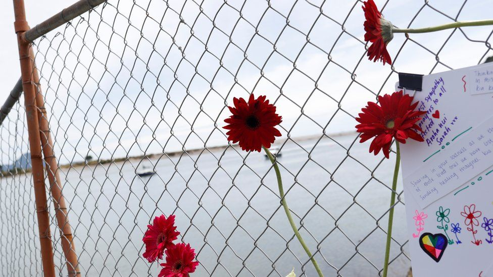 Flowers and cards at a fence