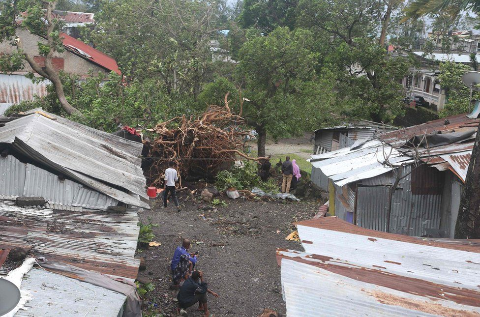 People stand by damaged houses and fallen trees after tropical storm Kenneth hit Comoros