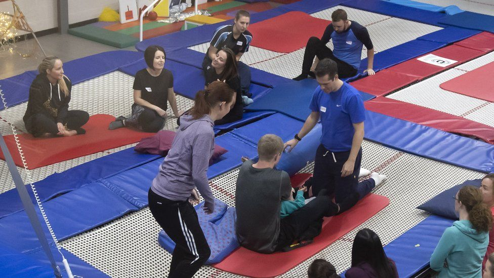 A couple of members of staff supporting a student on the trampoline