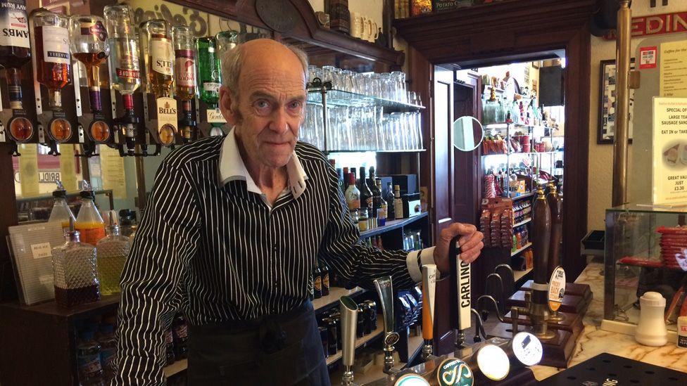 John Sadler behind the bar