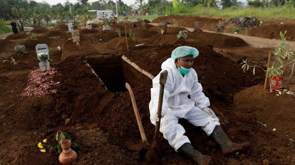 A gravedigger wearing personal protective equipment rests