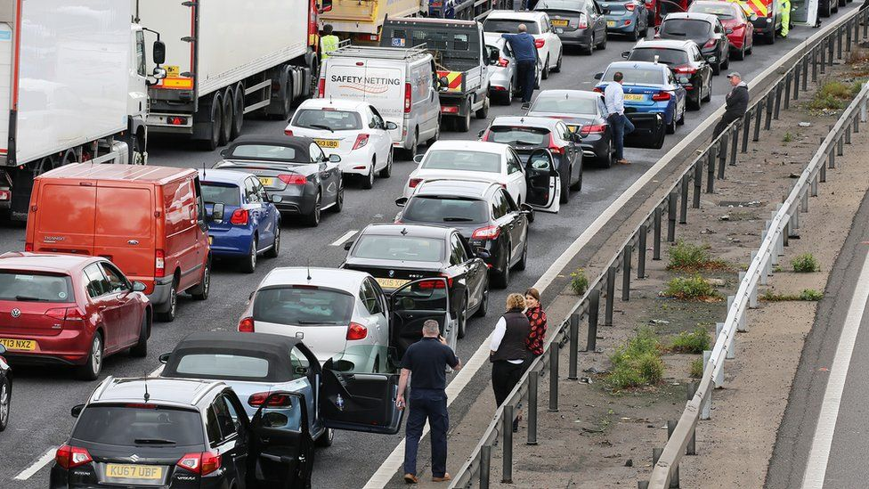Motorists talk on the side of the road next to stranded cars