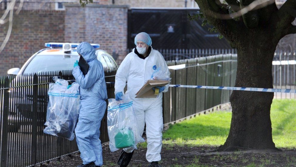 Forensic officers remove items of evidence including a green petrol can after searching an area where a man was found on fire near Kensington Palace in the early hours of Tuesday morning