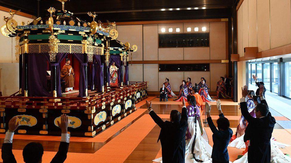 "Japan""s Prime Minister Shinzo Abe (R) shouts banzai cheer for Emperor Naruhito (top L) and Empress Masako"