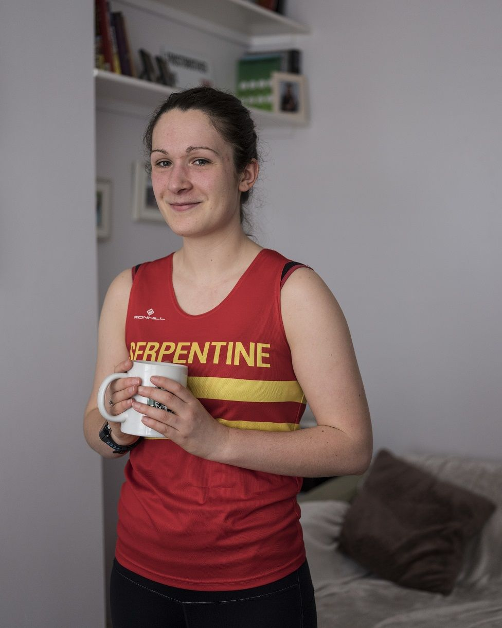 Photo of Coralie Frost at home with a cup of coffee in running gear