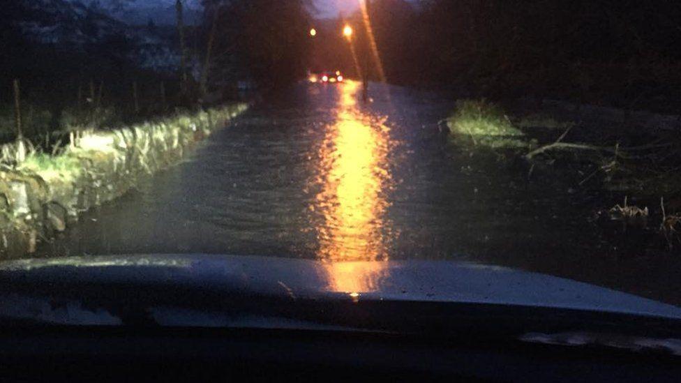 Car driving down a flooded street