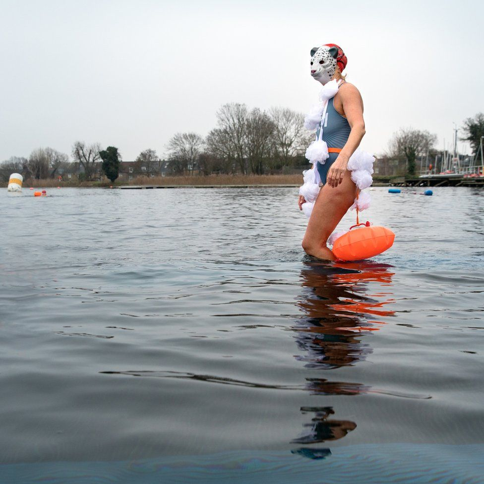 An image of a woman walking into a lake whilst wearing a bathing suit and a mask