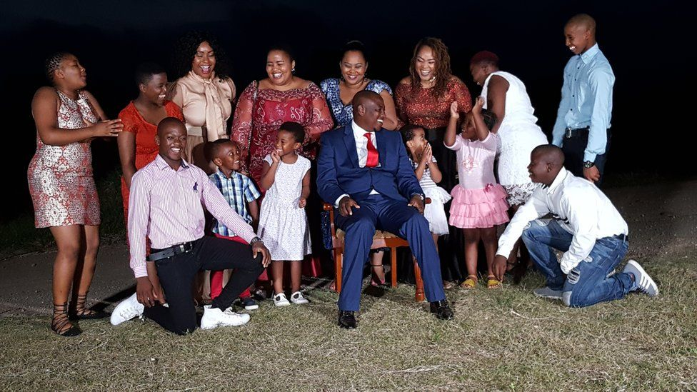 The whole Mseleku family including children pose for a photo in their garden