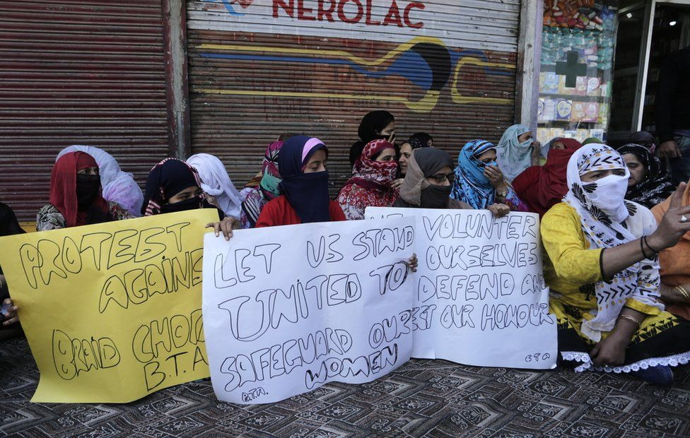 "Kashmiri Muslim women hold signs protesting against ""braid chopping"""