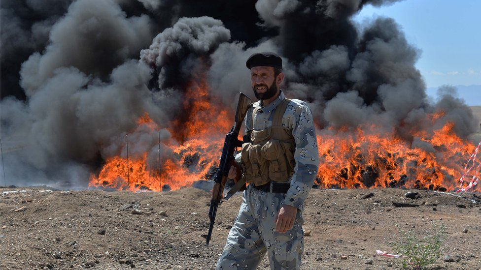 An Afghan security personnel stands guard as seized drugs and alcoholic drinks burn on the outskirts of Jalalabad