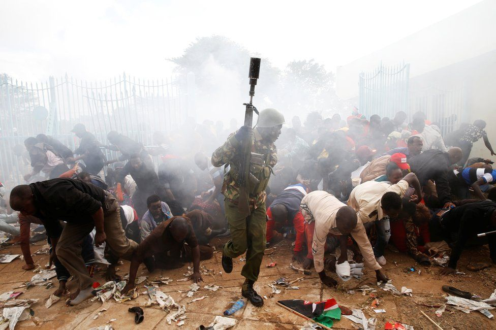People fall as police fire tear gas to try control a crowd trying to force their way into a stadium to attend the inauguration of President Uhuru Kenyatta in Nairobi, Kenya, 28 November