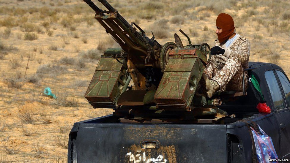 """militia sits on a pick up truck mounted with a machine gun during clashes with forces loyal to Libya""""s government"""