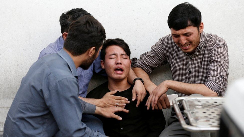 People comfort a distressed man at the scene