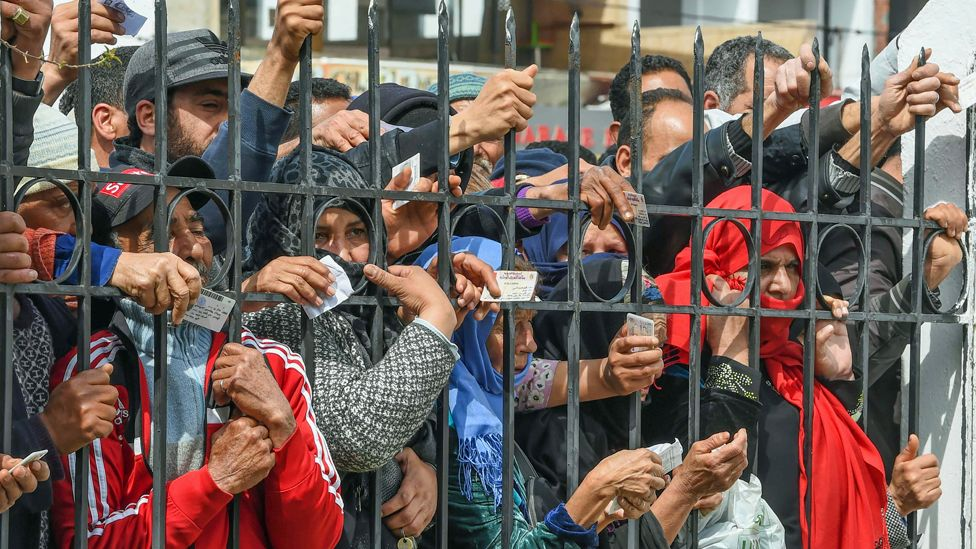 People holding their ID cards outside a government building in Mnihla, Tunisia - Monday 30 March 2020