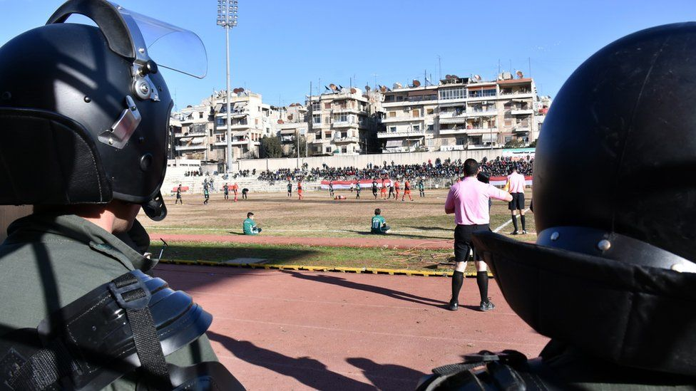 The helmets of two Syrian police, in full riot gear, are seen watching the football game from the sidelines