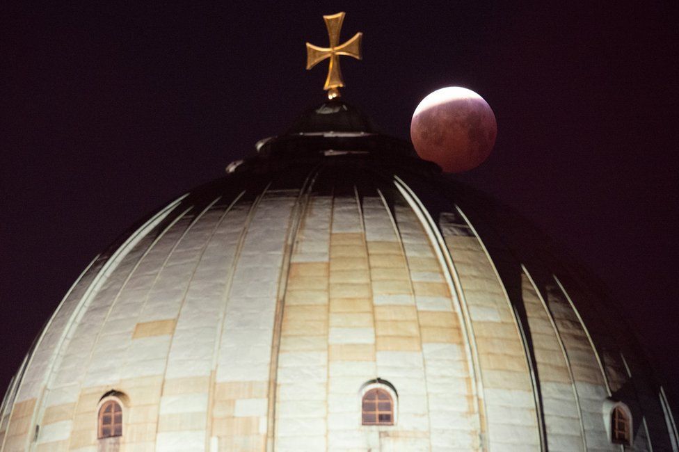 A view of the lunar eclipse above the St Elizabeth Church in Nuremberg, Germany
