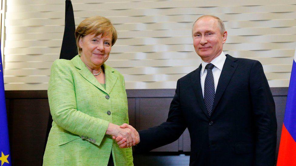 Merkel shakes hands with Putin
