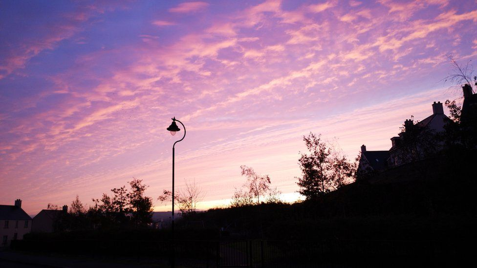 Silhouette of a residential street at dawn with Stratocumulus cloud formation.