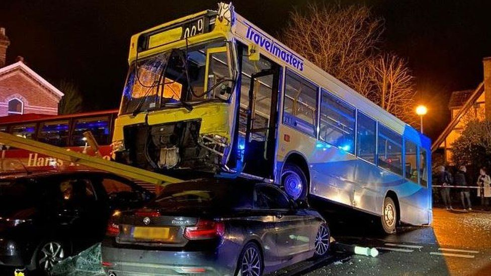 A photo of a bus on top of a parked car