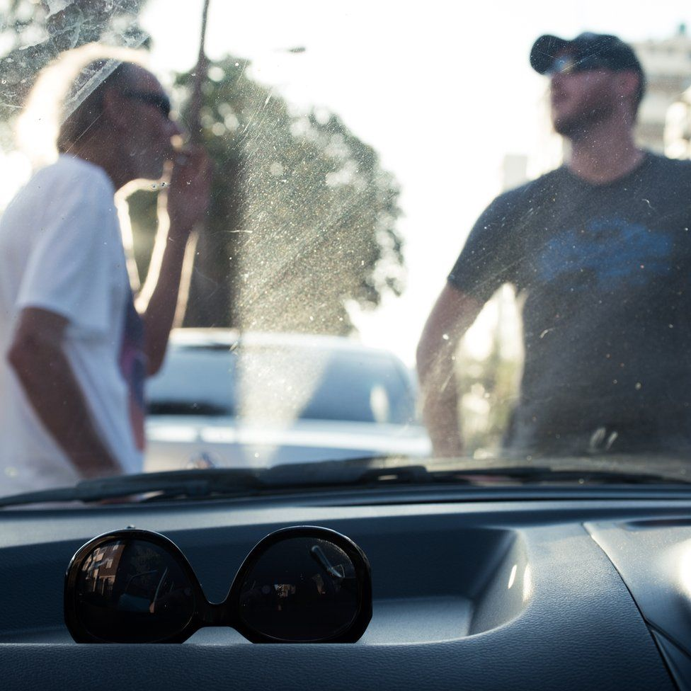 Two men pictured through the windscreen of a car