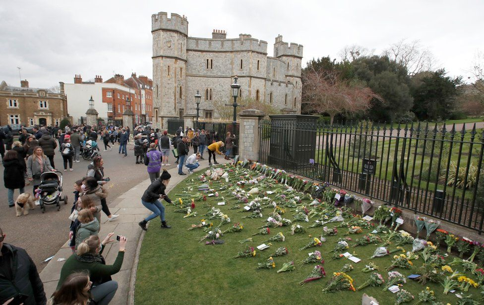 Mourners gather outside Windsor Castle after Britain's Prince Philip, husband of Queen Elizabeth, died at the age of 99, in Windsor, near London. 10 April 2020.
