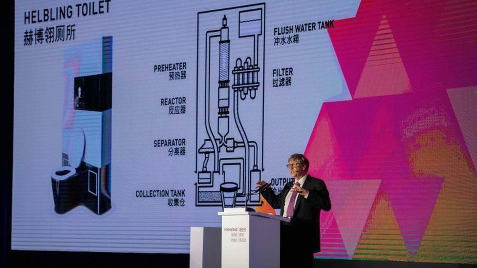 Bill Gates stands in front of a screen with a model of a 'Helbling' toilet at event