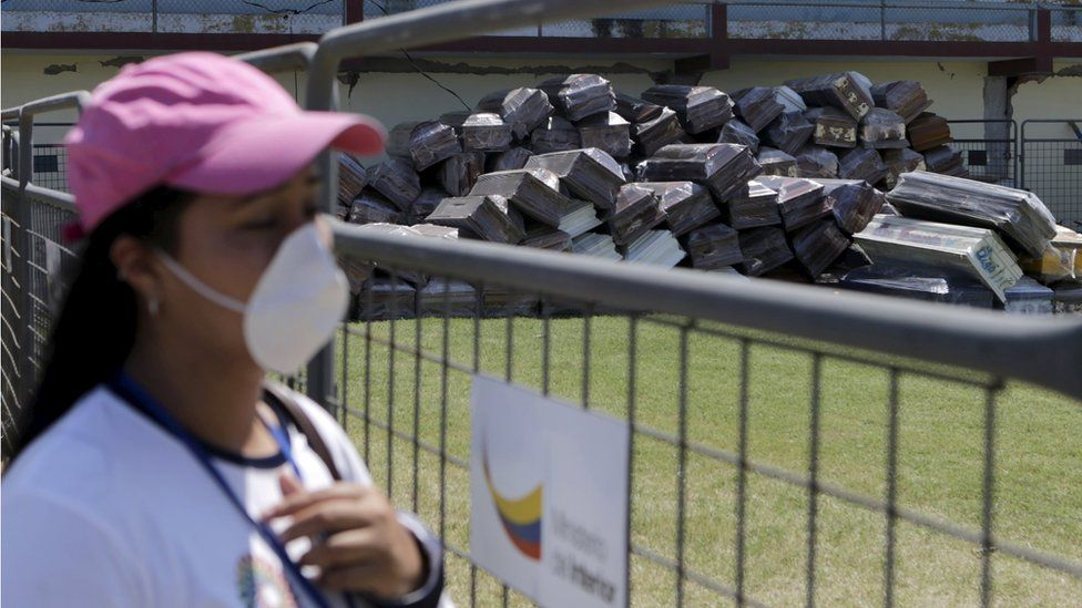 """A woman looks at a pile of empty coffins at Maximino Puertas stadium in Pedernales, after an earthquake struck off Ecuador""""s Pacific coast, April 19, 2016"""