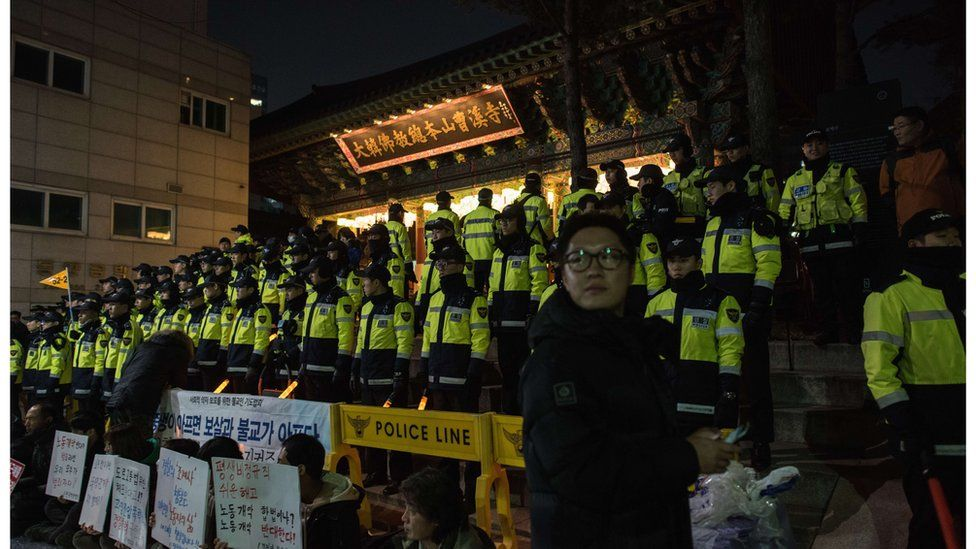 Hundreds of police officers form a cordon outside the temple compound on Wednesday night