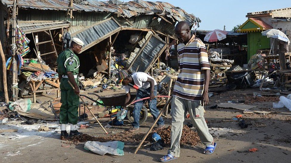 A man walks past a the scene of a bombing after at least 20 people were killed when a young female suicide bomber detonated her explosives at a bus station in Maiduguri, northeast Nigeria, on June 22, 2015 in an attack likely to be blamed on Boko Haram