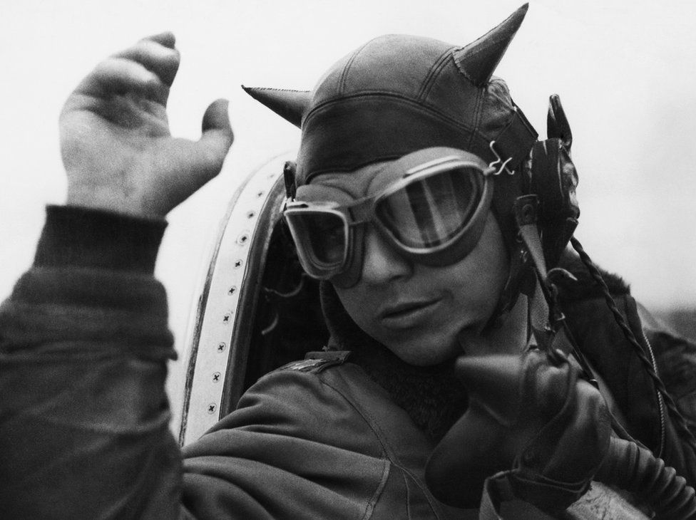 Lieutenant Colonel Louis Houck dons his 'devil's helmet' prior to a mission.