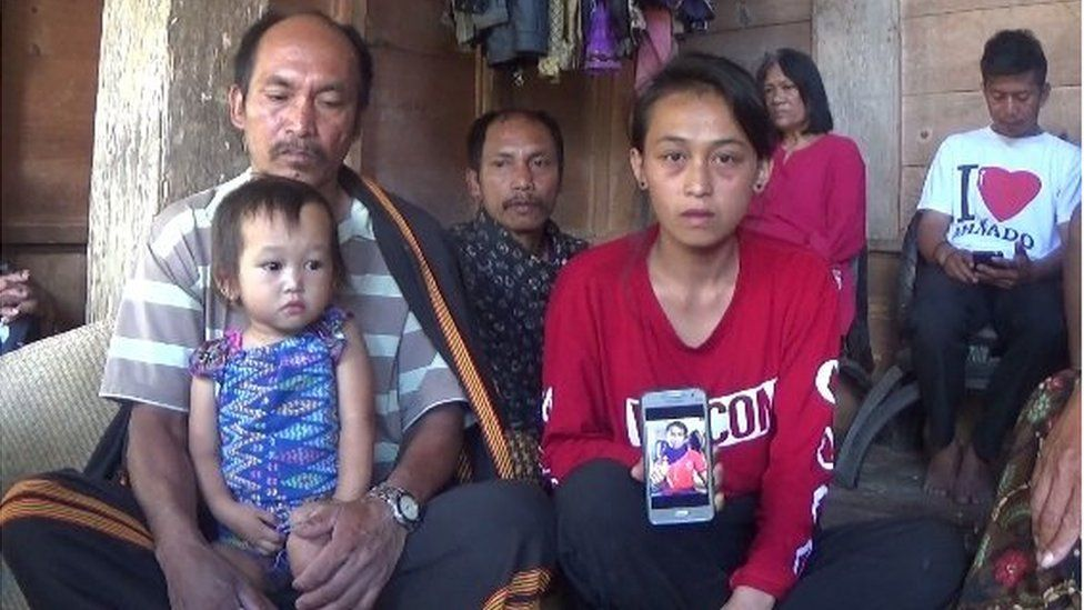 Anita Limbu Datu (R) shows a picture of her husband Alpianus, who was killed in the separatist attack