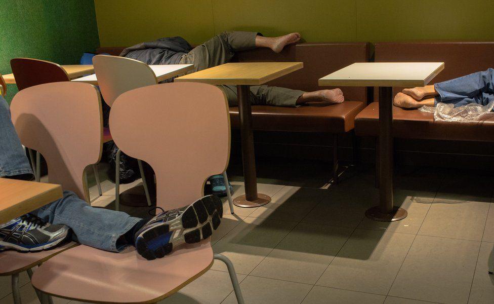People lying down to sleep on seating in McDonald's
