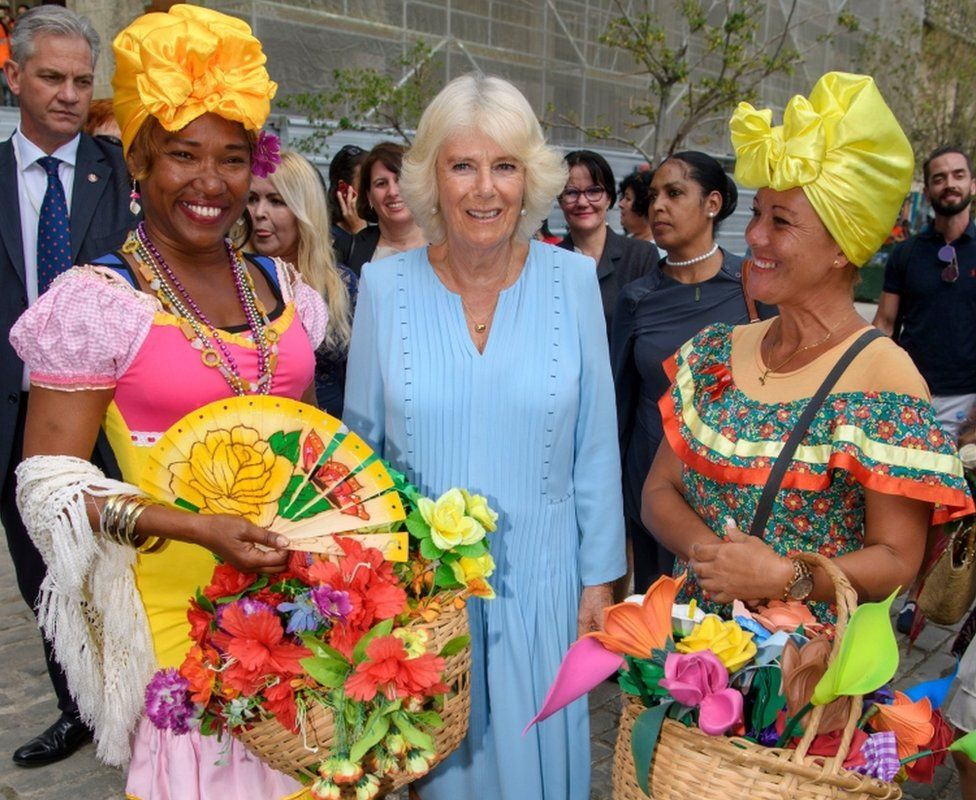 Camilla poses with two ladies in traditional Cuban clothing