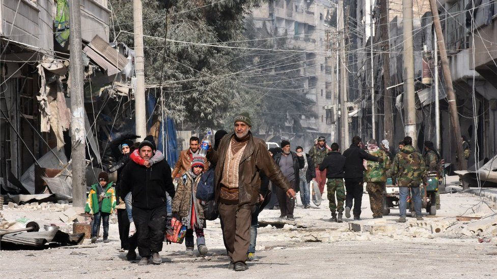 Syrian residents flee violence in Aleppo's eastern Saliheen neighbourhood on December 12, 2016 after regime troops retook the area from rebel fighters.