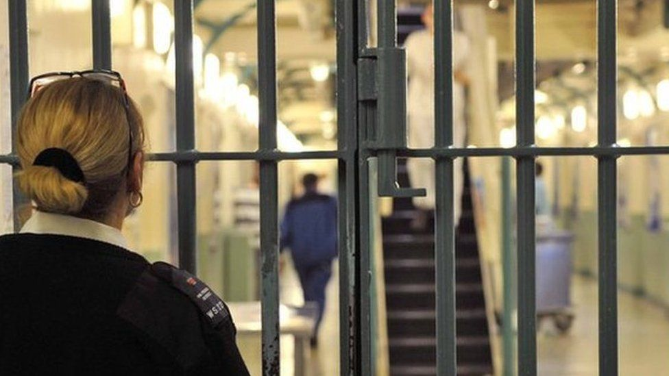 An anonymous female prison officer locks a door at Wormwood Scrubs