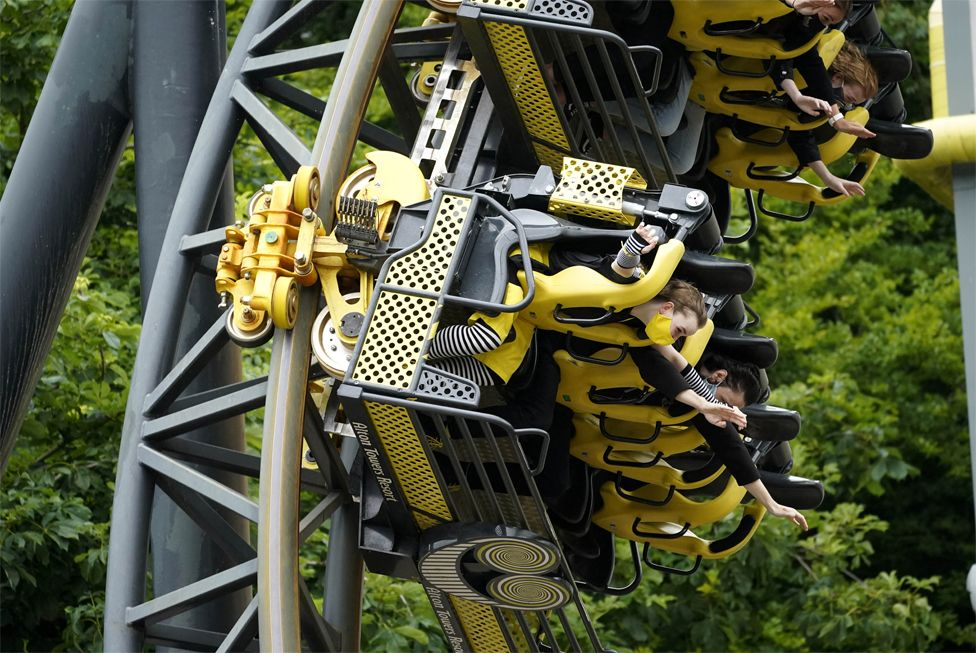 People ride a rollercoaster