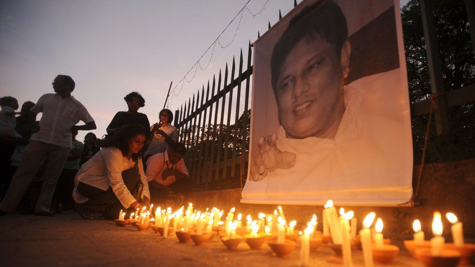 Sri Lankan journalists and well wishers light candles in front of a photograph of slain editor Lasantha Wickrematunge