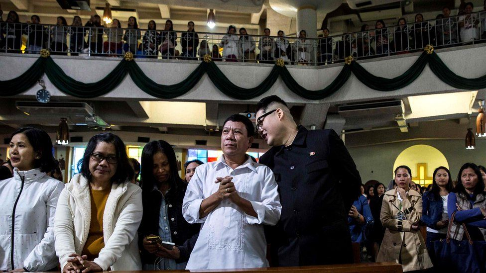 A Philippine President Rodrigo Duterte impersonator (centre left), who goes by the name Cresencio Extreme, listens to a North Korean leader Kim Jong-un impersonator (centre right), who goes by the name Howard X, as they attend a church service in the Central district of Hong Kong, 3 February 2019