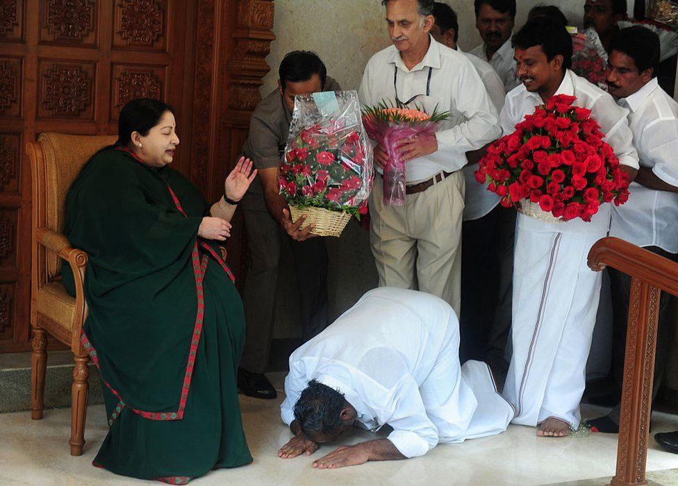 A party cadre prostrates himself at the feet of All India Anna Dravida Munnetra Kazhagam(AIADMK) leader Jayalalithaa Jayaram as she gestures at her residence in Chennai on May 19, 2016.