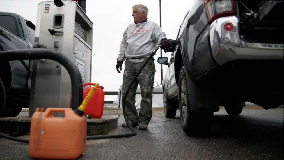 man filling care with fuel