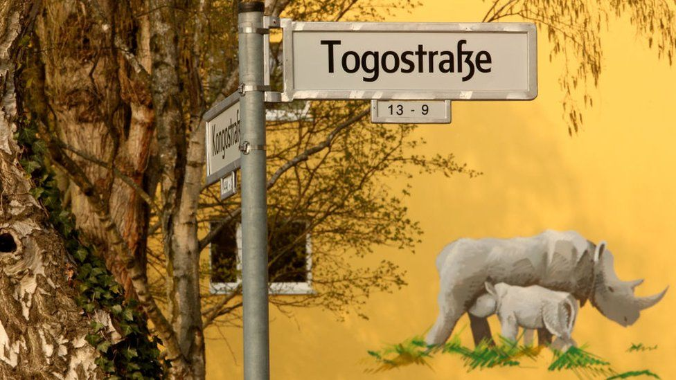 A street sign indicating a street named after the country of Togo is seen in front of a mural of a nursing rhinoceros on April 14, 2018 in Berlin, Germany.