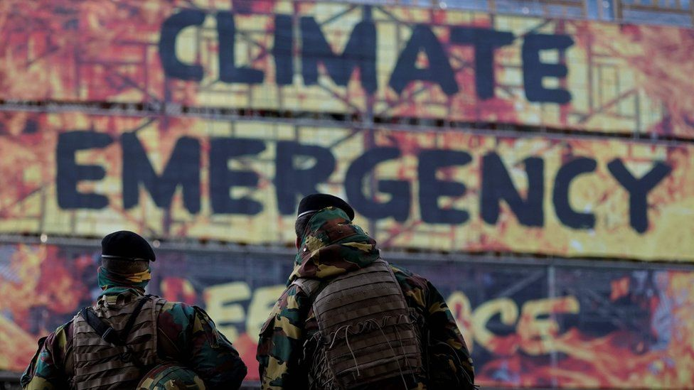 Two soldiers look at a group of activists of the environmental NGO Greenpeace taking part in a protest action after attaching a banner on the frontage of the European Council building, in Brussels
